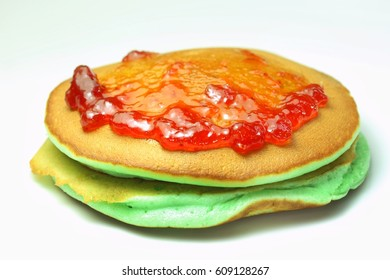 Pancake served with strawberry topping, green pancakes on white background, selective focus.