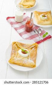Pancake small envelopes stuffed with sour cream and homemade jam from rhubarb