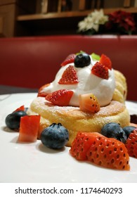 Pancake with strawberry, blueberry, berry sauce, mascarpone cheese cream and maple syrup.