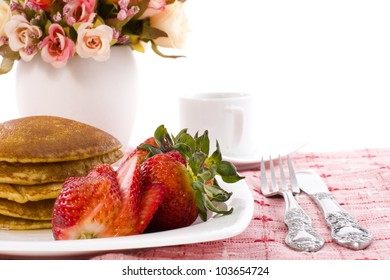 Pancake and strawberry have maple syrup on top with coffee