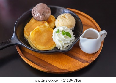 pancake with vanilla chocolate ice cream, honey and mint on pan and wood dish on table