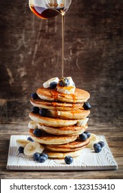 Pancakes with banana, blueberry and maple syrup for a breakfast.
