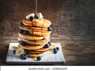 Pancakes with banana, blueberry and maple syrup for a breakfast, wooden background, copy space