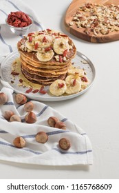 Pancakes with banana, walnuts, goji and honey. Healthy breakfast. On white wooden table background. Top view