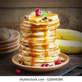 Pancakes with banana,walnut and caramel for a breakfast on a dark wooden background rustic style