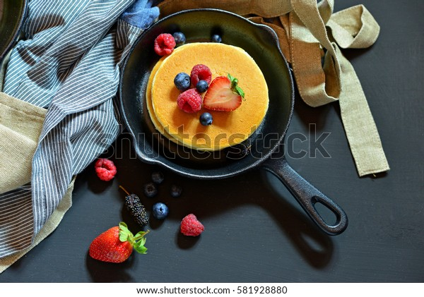 Pancakes with berries in the black pan. Decorated with tablecloth and fresh Strawberries, Raspberry, Blueberry.