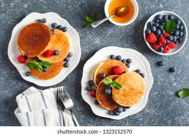 Pancakes with berries and honey, top view.