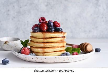 Crêpes avec baies et sirop d'érable pour le petit-déjeuner sur fond clair.