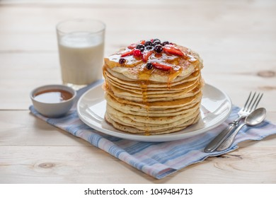 Pancakes with berries and maple syrup on a light table. Pancakes and milk.