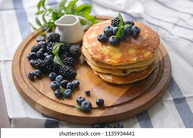 Pancakes and berries on the board with honey - top view
