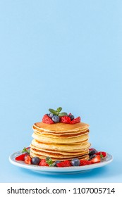 Pancakes with berries on a bright pastel background, copy space.