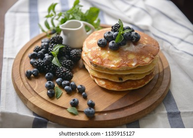 Pancakes with blackberries, blueberries and mint on a chalkboard