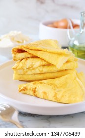 Pancakes (blinis) without flour and ingredients: cream cheese, olive oil and eggs on light background