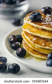 Pancakes with blueberries and honey on a plate on white background closeup