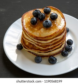 Pancakes with blueberries and honey on white round plate on dark wooden background, side view. Close-up.