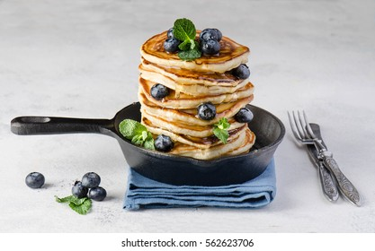Pancakes with blueberries and leafs of mint in a small pan on white background. Breakfast