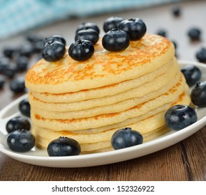 Pancakes with blueberries on a brown background