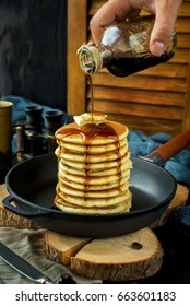 Pancakes with butter in the black pan. Decorated with tablecloth on a dark background. With hand pouring maple syrup