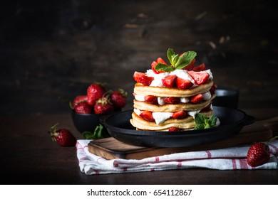Pancakes cake with mascarpone and strawberries. Dark rustic background.