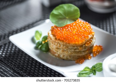 "Pancakes with caviar in ""Russian style"" on dark background."