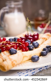 pancakes with cherry,blueberry and red currant and pitcher of milk