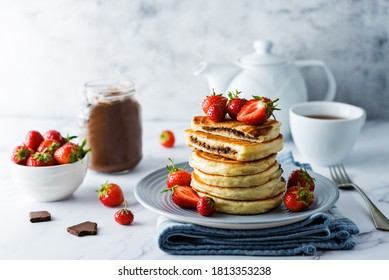 Pancakes with chocolate nutella filling decorated with strawberries. toning. selective focus
