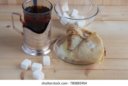 Pancakes with condensed milk and a Cup of tea with cubes of sugar on a wooden table