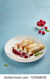 pancakes with cottage cheese. decorated with raspberry sauce and sour cream