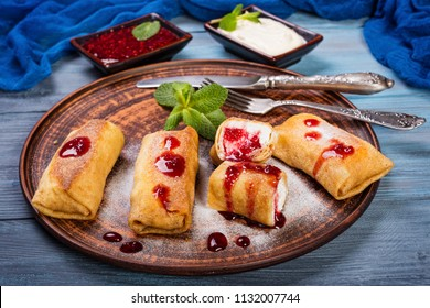 Pancakes with cottage cheese and jam in a clay dish on a blue wooden background