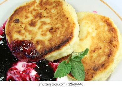 Pancakes from cottage cheese with jam, sour cream and leaves of mint.