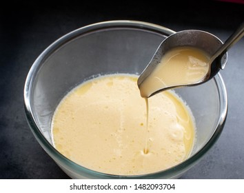 Pancakes or crepe raw dough on dark  background.