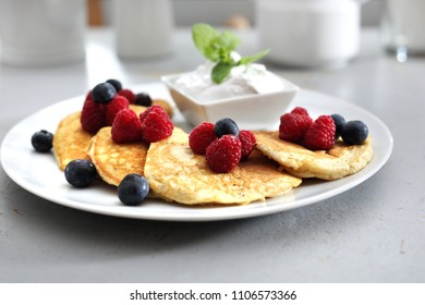 Pancakes, diet pancakes with fruit. A portion of tasty pancakes decorated with berries of raspberries and blueberries, served with yoghurt sauce