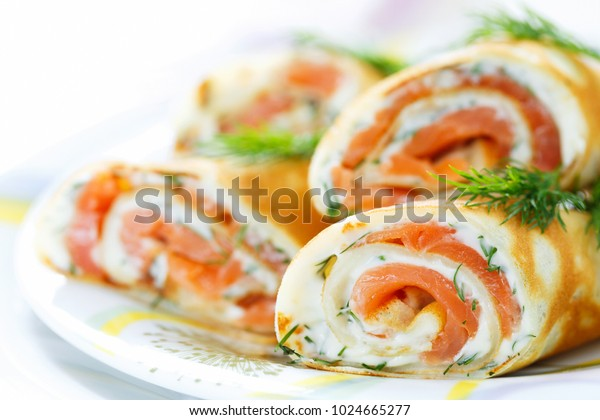 Pancakes with fish salmon, cheese and dill. Macro. Space for text