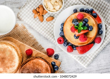 Pancakes with forest fruits berries on white table. Top view of fresh pancakes on cloath with almonds. Blueberries, raspberries on pancakes.