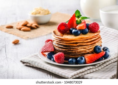 Pancakes with forest fruits berries on white table. Fresh pancakes on cloath with almonds. Blueberries, raspberries on pancakes.