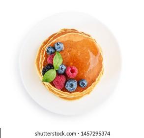 Pfannkuchen mit frischen Beeren und Ahornsirup auf dem Teller einzeln auf weißem Hintergrund, Draufsicht