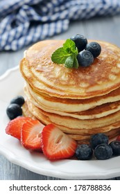 Pancakes with fresh berries, mint and maple syrup on white plate closeup