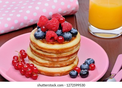 Pancakes with fresh berries and orange juice on table
