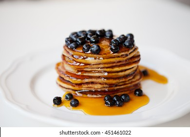 Pancakes with fresh blueberries and honey for breakfast