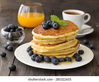 Pancakes with fresh blueberries and honey on wooden table