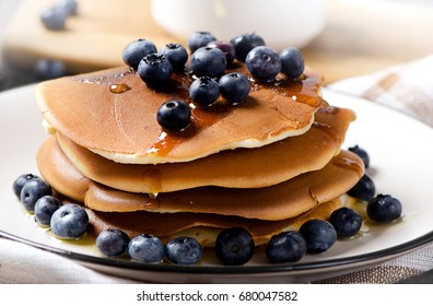 Pancakes with fresh blueberry and honey on wooden table.