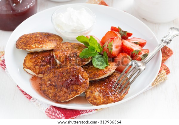 Pancakes with fresh strawberries, jam and tea, close-up