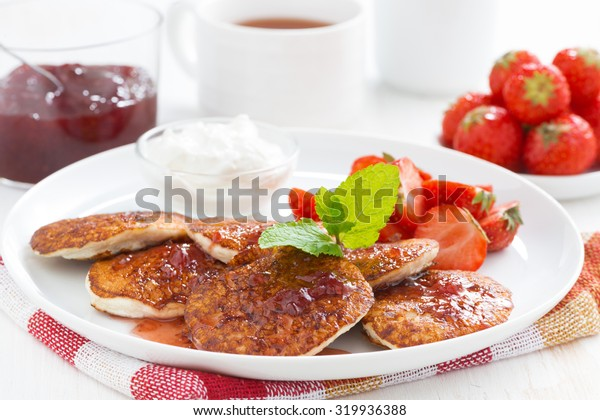 Pancakes with fresh strawberries on a plate, jam and tea, close-up, horizontal