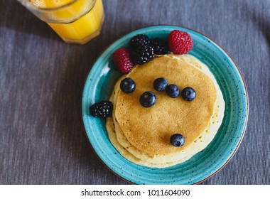 Pancakes, fresh wild berries and orange juice. Breakfast
