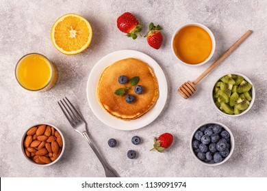 Pancakes with fruit, honey, nuts. Top view.