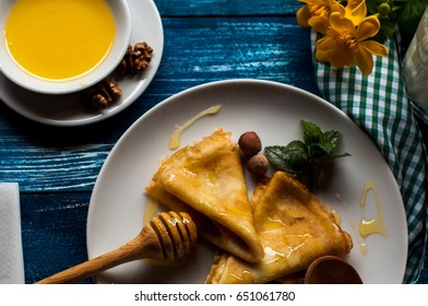 pancakes with honey syrup on a white plate. traditional crepe for pancake week or Shrovetide. crepes with roasted nuts