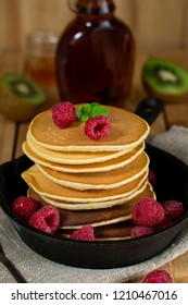 Pancakes hotcakes with fresh berries and fruit served with maple syrup