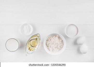 Pancakes ingredients on white background. Milk, flour, eggs, baking soda, sugar and vegetable oil.