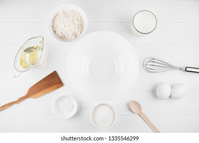 Pancakes ingredients on white background. Milk, flour, eggs, baking soda, sugar and vegetable oil and bowl in the centre.