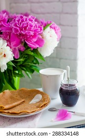 Pancakes with jam and a cup of milk on a tray on a background of a bouquet of peonies